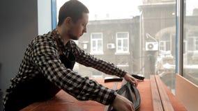 Le maître met les blancs en cuir sous la ceinture sur la table Fabrication de ceinture en cuir banque de vidéos
