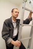 Le maître monte une échelle vers le haut. Réparez d'intérieur Photographie stock libre de droits