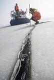 Le maître nageur masculin mesure l'épaisseur de glace Photographie stock