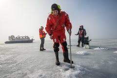 Le maître nageur masculin mesure l'épaisseur de glace Photos libres de droits