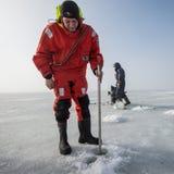 Le maître nageur masculin mesure l'épaisseur de glace Photo stock