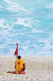 Le maître nageur s'assied sur la plage photos stock