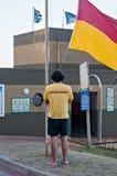 Le maître nageur soulevant le drapeau à la station de secours en bronze de ressac de plage dans Umhlanga bascule Images libres de droits