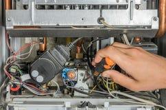 Le maître répare la composante électronique de la chaudière de chauffage au gaz photographie stock libre de droits