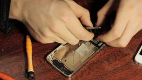 Le maître répare le téléphone portable Puces et détails du smartphone banque de vidéos