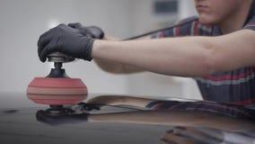 Le maître rectifie un toit d'automobile noire propre pendant la fabrication du revêtement de protection dans un garage banque de vidéos