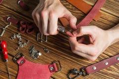 Le maître tient dans des ses mains un couteau et un morceau de cuir Sur la table en bois brune a dispersé avec des outils et des  Photo stock