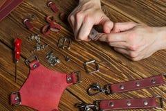 Le maître tient dans des ses mains un couteau et un morceau de cuir Sur la table en bois brune a dispersé avec des outils et des  Photo libre de droits