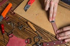 Le maître tient dans des ses mains un couteau et un morceau de cuir Sur la table en bois brune a dispersé avec des outils et des  Image stock