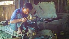 Le maître travaille à un grand couteau dans la forge Photo stock