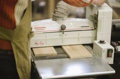 Le maître travaille à une machine de rectification superficielle photographie stock