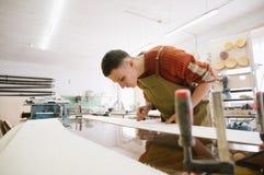 Le maître travaille à une machine de rectification superficielle images libres de droits