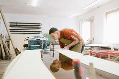 Le maître travaille à une machine de rectification superficielle image libre de droits