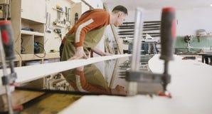 Le maître travaille à une machine de rectification superficielle photographie stock libre de droits