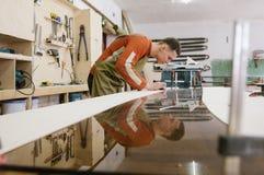 Le maître travaille à une machine de rectification superficielle images stock