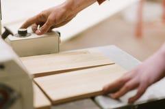 Le maître travaille à une machine de rectification superficielle dans l'atelier de menuiserie photos stock