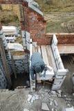 Le maître, utilisant une truelle, colle des gasblocks avec une solution visqueuse au chantier de construction photographie stock libre de droits