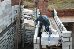 Le maître, utilisant une truelle, colle des gasblocks avec une solution visqueuse au chantier de construction image libre de droits