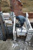Le maître, utilisant une truelle, colle des gasblocks avec une solution visqueuse au chantier de construction photos stock
