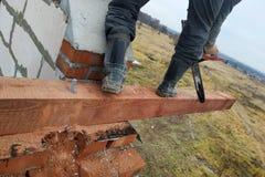Le maître utilise une scie pour manipuler et couper la poutre de bois de construction image libre de droits