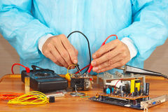 Le maître vérifie le conseil électronique avec le multimètre dans l'atelier de service Photographie stock