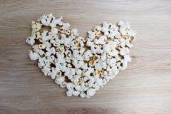 Le maïs éclaté a arrangé dans une forme de coeur sur en bois photographie stock libre de droits