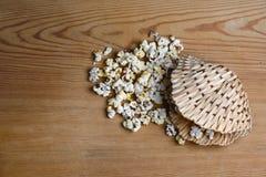 Le maïs éclaté de caramel sur le fond en bois de table, caramel a assaisonné le maïs éclaté dans un panier en osier sous forme de photographie stock