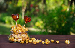 Le maïs éclaté et la sucrerie de caramel à un coeur forment lucettes Concept romantique Concept de fête Photo stock
