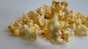 Le maïs éclaté pilote le gourmet sur un mouvement lent de fond blanc banque de vidéos
