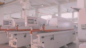 Le macchine per la lavorazione del legno del magazzino, nuove macchine per la lavorazione del legno stanno in una fila in azione archivi video