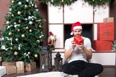 Le macho avec les yeux fermés tiennent la boîte actuelle à l'arbre de Noël image libre de droits