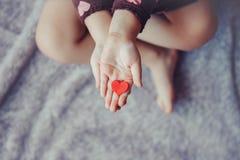 Le macro de l'enfant avec le parent adulte remet des paumes tenant un groupe de petits coeurs de papier rouges et pourpres de mou Image stock