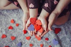 Le macro de l'enfant avec le parent adulte remet des paumes tenant un groupe de petits coeurs de papier rouges et pourpres de mou Images stock