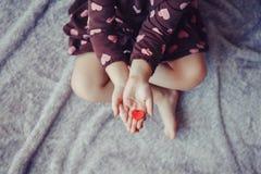 Le macro de l'enfant avec le parent adulte remet des paumes tenant un groupe de petits coeurs de papier rouges et pourpres de mou Photographie stock