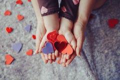 Le macro de l'enfant avec le parent adulte remet des paumes tenant un groupe de petits coeurs de papier rouges et pourpres de mou Photos stock