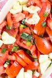Le macro de plan rapproché a coupé en tranches la tomate et la salade d'oignons sur la table Image stock