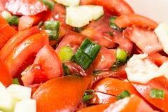 Le macro de plan rapproché a coupé en tranches la tomate et la salade d'oignons sur la table Image libre de droits