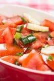 Le macro de plan rapproché a coupé en tranches la tomate et la salade d'oignons sur la table Photographie stock