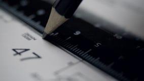 Le macro ingénieur trace la ligne droite sur le papier avec le plan banque de vidéos