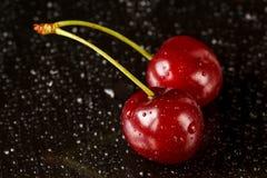 Le macro tir de deux cerises mûres délicieuses sur un fond réfléchi noir avec de l'eau se laisse tomber Images stock