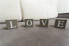 Le macro tir de l'amour de mot a orthographié par des lettres sur les briques en bois Images libres de droits