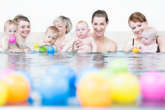 Le madri ed i lattanti al bambino nuotano il corso che gioca con le palle Fotografia Stock