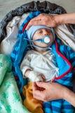 Le madri passa giudicare un ragazzo infantile malato paziente con una tettarella e una fasciatura sulla sua mano Fotografie Stock Libere da Diritti