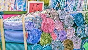 Le magasin traditionnel de tissu avec des piles de textiles colorés, petits pains de tissu au marché calent - le fond d'industrie Photos libres de droits