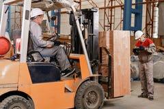 Le magasinier marque l'arrivée sur le comprimé Équipez conduire un chariot élévateur par un entrepôt dans une usine conducteur de images stock