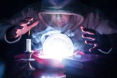 Le magicien avec le capot et les lumières fument la boule de cristal magique images libres de droits