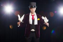 Le magicien avec deux colombes blanches volantes Sur un fond noir images libres de droits