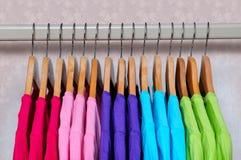 Le magliette multicolori delle donne che appendono sui ganci di legno Fotografie Stock Libere da Diritti