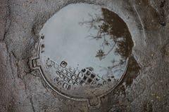 Le magma sur le trou d'homme dans la surface d'asphalte Photos stock