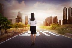 Le main-d'œuvre féminine commence à marcher son voyage sur une rue au succès Photographie stock